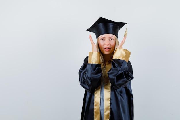 Blondynka, rozciąganie rąk w pobliżu twarzy w sukni i czapce ukończenia szkoły i patrząc szczęśliwy.