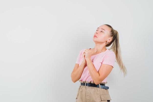 Blondynka, ściskając ręce w geście modlitwy w t-shirt, spodnie i patrząc z nadzieją. przedni widok.