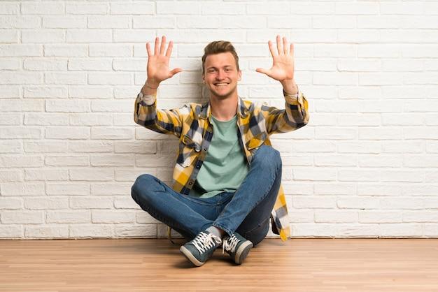 Blondynka siedzi na podłodze licząc dziesięć palcami