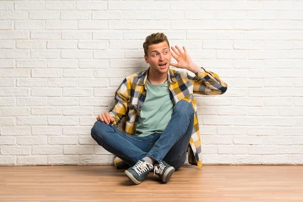 Blondynka siedzi na podłodze, słuchając czegoś, kładąc rękę na uchu