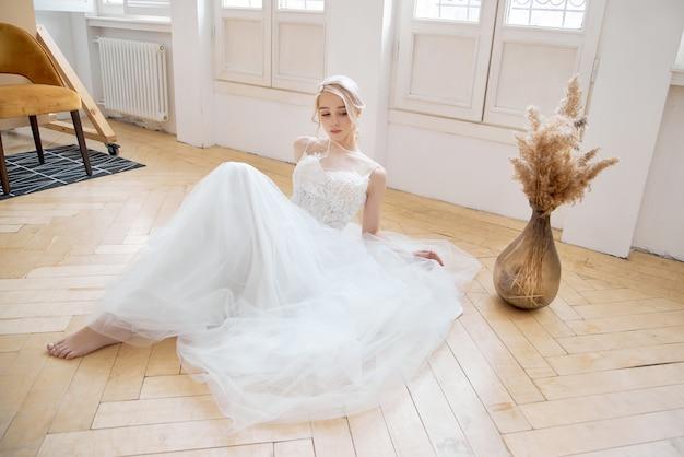 Blondynka siedzi na podłodze w pięknej białej sukni ślubnej