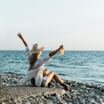 Blondynka siedzi na skałach z sokiem, patrząc na morze