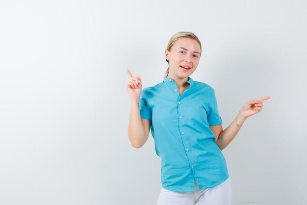 Blondynka skierowana w górę i w prawo palcami wskazującymi w niebieskiej bluzce na białym tle