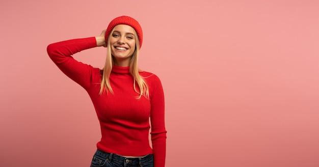 Blondynka śliczna dziewczyna uśmiecha się czerwony kapelusz i sweter