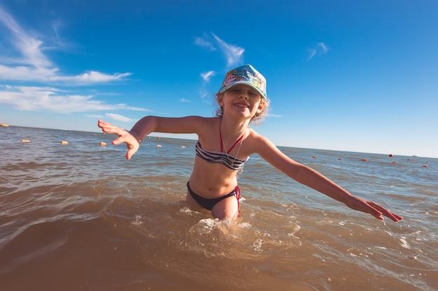 Blondynka śliczna siedmioletnia dziewczynka bawi się i dobrze bawi się nad morzem podczas wakacji.