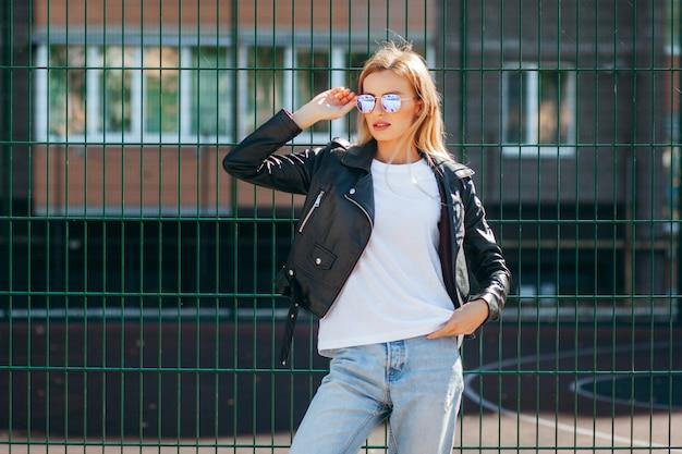 Blondynka sobie t-shirt, okulary i skórzaną kurtkę pozuje przeciwko ulicy