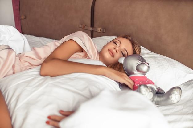 Blondynka śpi ze srebrnym niedźwiedziem w łóżku. dzień dobry. sen i odpoczynek