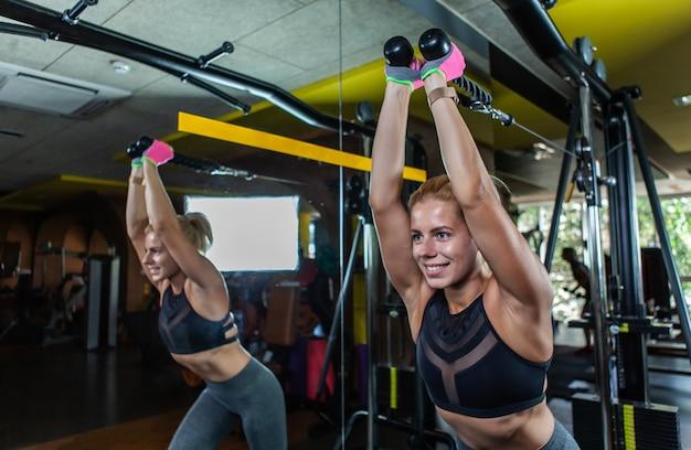 Blondynka sprawna kobieta robi ćwiczenia na triceps na maszynie kablowej na siłowni.