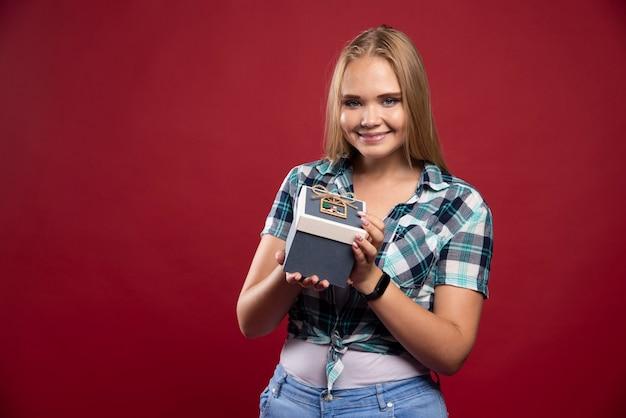 Blondynka staje się szczęśliwsza i zaskoczona, gdy otrzymała pudełko z prezentem.