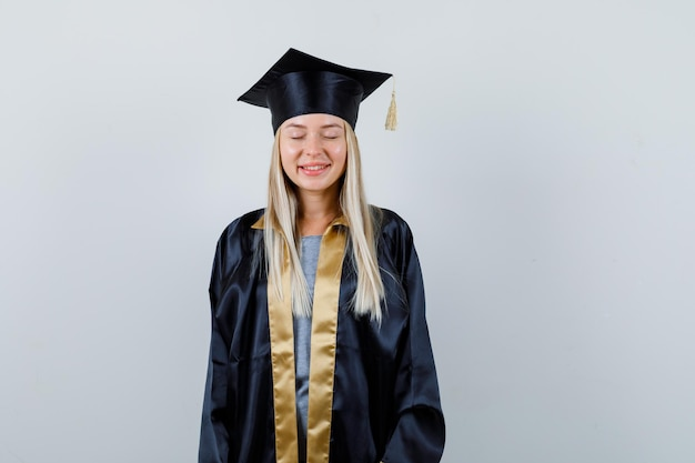 Blondynka stoi prosto, zamykając oczy i pozowanie na kamery w sukni i czapce ukończenia szkoły i patrząc szczęśliwy.