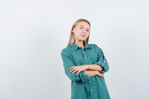 Blondynka stoi rękami skrzyżowanymi w zielonej bluzce i wygląda na szczęśliwą.
