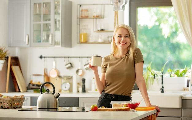 Blondynka stoi w kuchni przy filiżance kawy