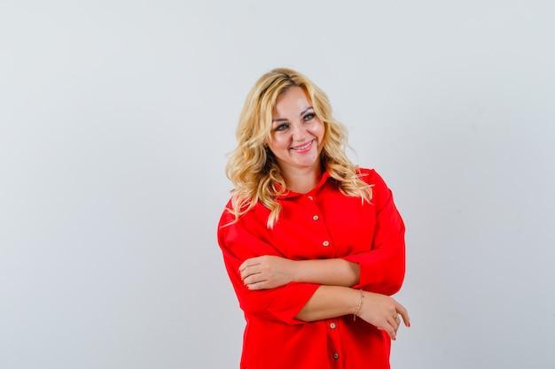 Blondynka stojąca prosto i pozowanie na kamery w czerwonej bluzce i patrząc szczęśliwy