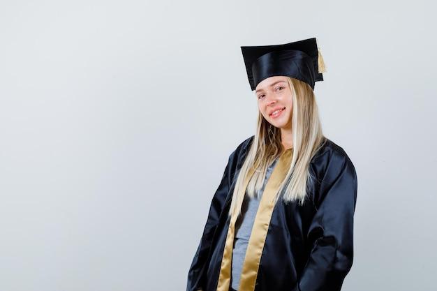 Blondynka stojąca prosto i pozowanie na kamery w sukni i czapce ukończenia szkoły i patrząc szczęśliwy.