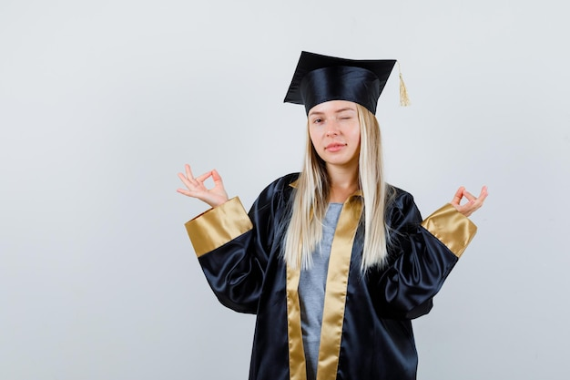 Blondynka stojąca w medytującej pozie, mrugająca w sukni i czapce ukończenia szkoły i wyglądająca na szczęśliwą