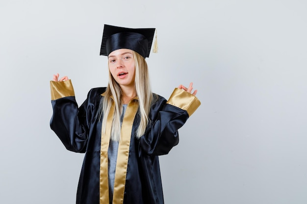 Blondynka stojąca w medytującej pozie w sukni i czapce ukończenia szkoły i wyglądająca na szczęśliwą