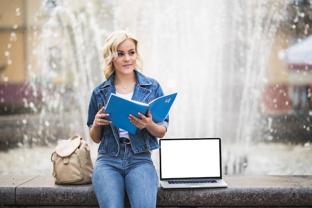 Blondynka studentka pracuje na swoim komputerze i czytać książkę w pobliżu fontanny w mieście w ciągu dnia