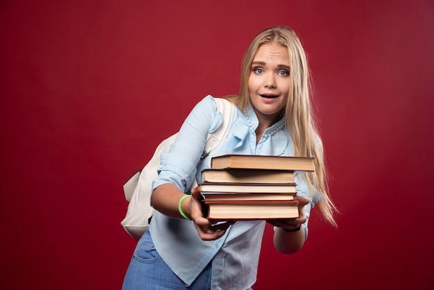 Blondynka studentka trzyma ciężki stos książek i wygląda na zmęczoną.
