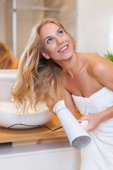 Blondynka suszy włosy po prysznicu
