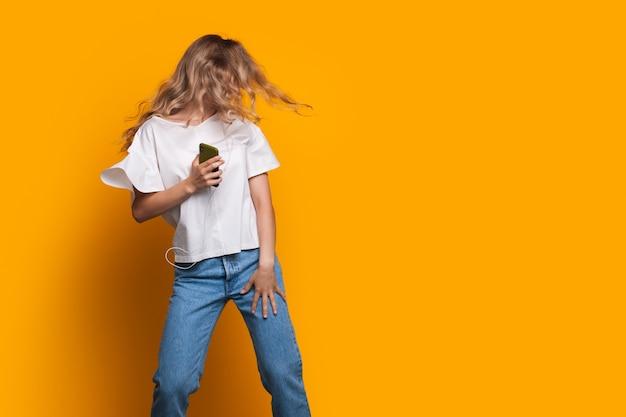 Blondynka tańczy na żółtej ścianie studia, trzymając telefon w pobliżu wolnego miejsca, reklamując coś
