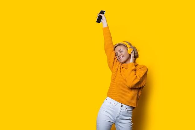 Blondynka tańczy na żółtej ścianie z wolną przestrzenią podczas słuchania muzyki przez słuchawki
