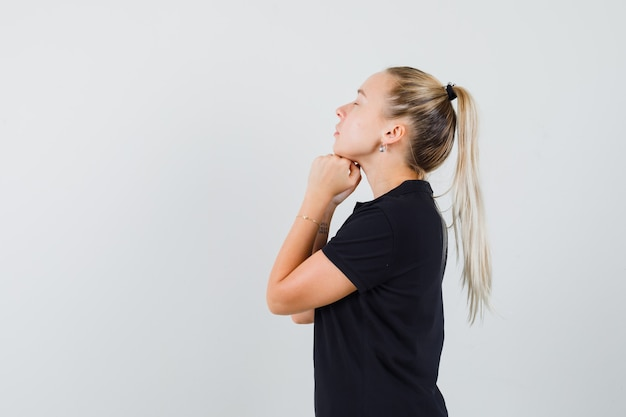 Blondynka trzyma ręce pod brodą w czarnej koszulce i wygląda na zrelaksowaną