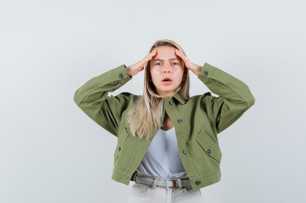 Blondynka trzyma ręce przy głowie w kurtce, spodniach i wygląda bolesnie, widok z przodu.
