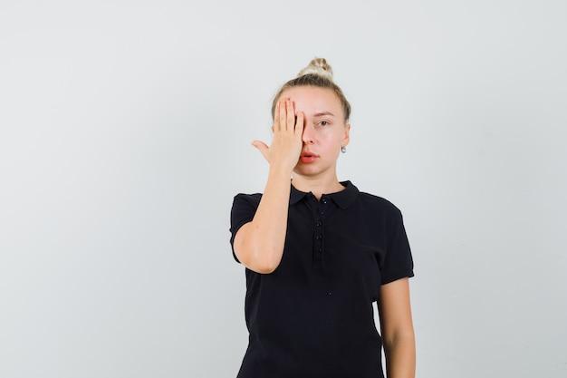 Blondynka trzyma rękę na jednym oku w widoku z przodu czarna koszulka.