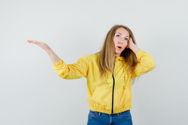 Blondynka trzyma rękę we włosach w kurtce, dżinsach i wygląda na zdezorientowanego.