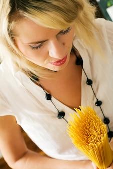Blondynka trzyma surowy makaron