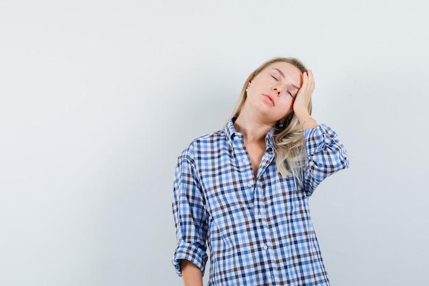 Blondynka, trzymając dłoń na głowie w dorywczo koszuli i patrząc śpiący