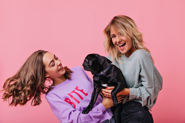 Blondynka, trzymając psa i śmiejąc się. wewnątrz portret wyrafinowanych pań, które bawią się razem i bawią się ze szczeniakiem.