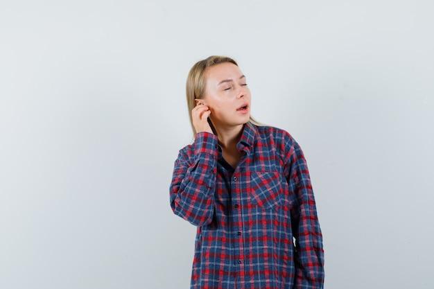 Blondynka trzymając rękę na uchu rozmawia przez telefon w kraciastej koszuli i patrząc skoncentrowany, widok z przodu.