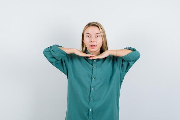 Blondynka trzymając się za ręce pod brodą w zielonej bluzce i ładnie wygląda.