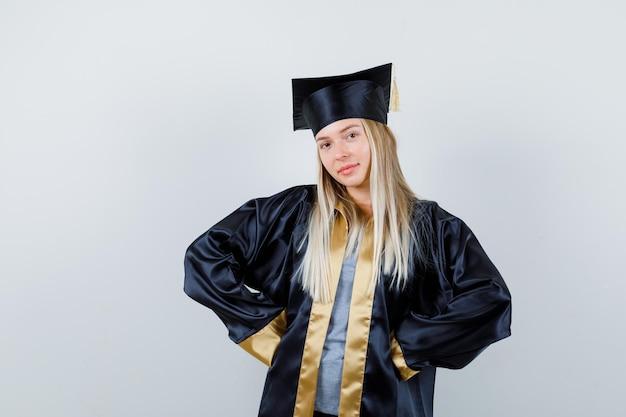 Blondynka, trzymając się za ręce w pasie w sukni i czapce ukończenia szkoły i wygląda ładnie.