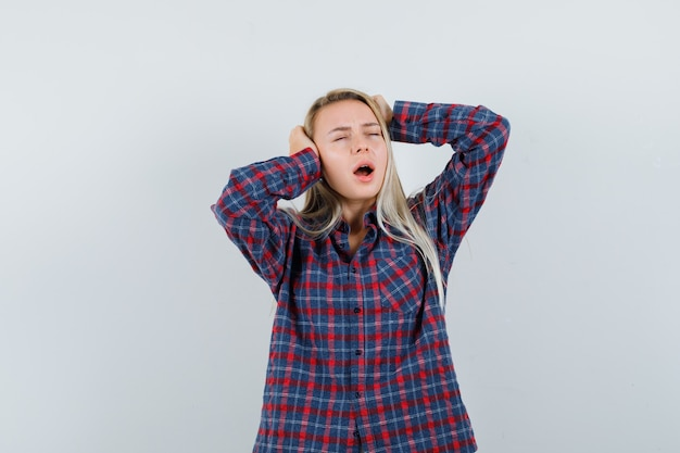 Blondynka trzymając się za uszy, stojąc z otwartymi ustami w kraciastej koszuli i patrząc na wyczerpaną, widok z przodu.