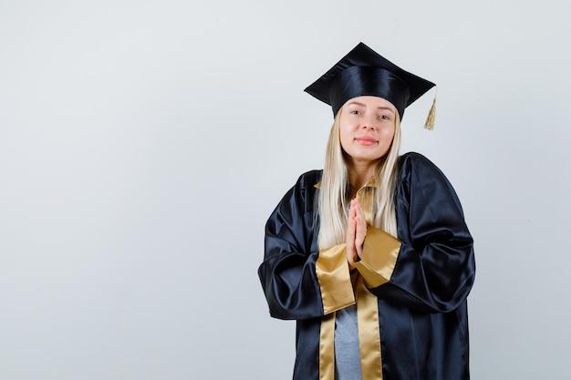 Blondynka trzymająca ręce w pozycji modlitewnej w sukni ukończenia szkoły i czapce i wyglądająca na szczęśliwą