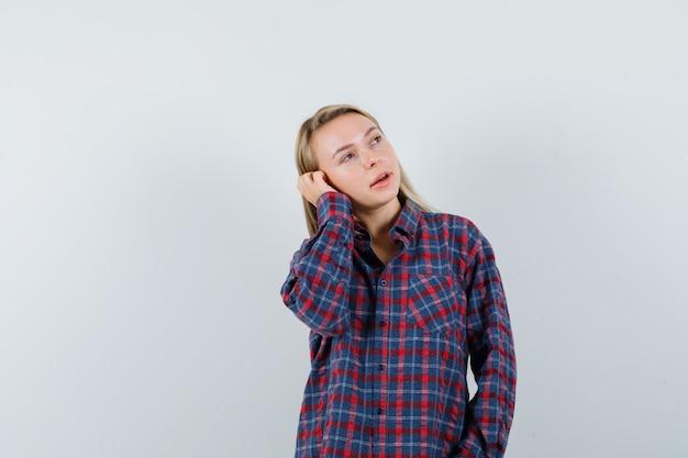 Blondynka trzymająca rękę na uchu, udająca rozmowę przez telefon w koszuli w kratkę i wyglądająca na skupioną. przedni widok.