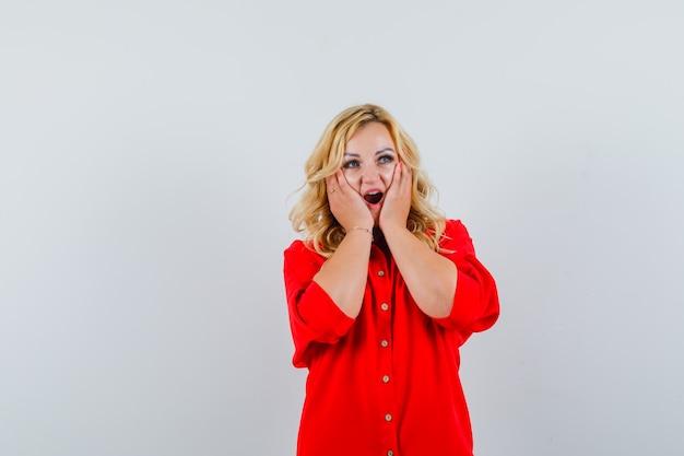 Blondynka trzymająca się za ręce na policzku, otwierająca usta w czerwonej bluzce i wyglądająca na zaskoczoną. przedni widok.