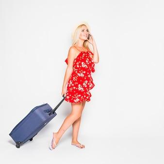 Blondynka turysta pozuje z walizką