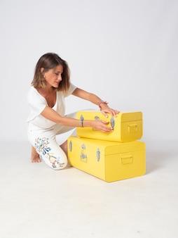 Blondynka ubrana na biało pozuje obok dwóch żółtych metalowych walizek.