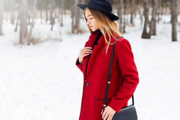 Blondynka ubrana w czerwony płaszcz na śnieżnym polu