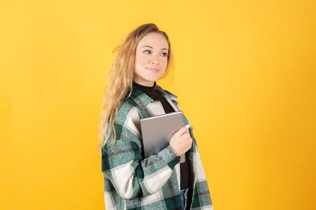 Blondynka, ubrana w ubranie, szczęśliwa trzymając tablet pod pachą, żółte tło