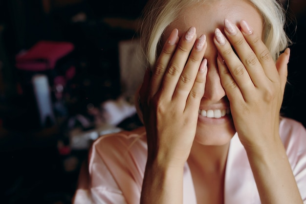 Blondynka uśmiecha się, gdy ukrywa twarz za palmami