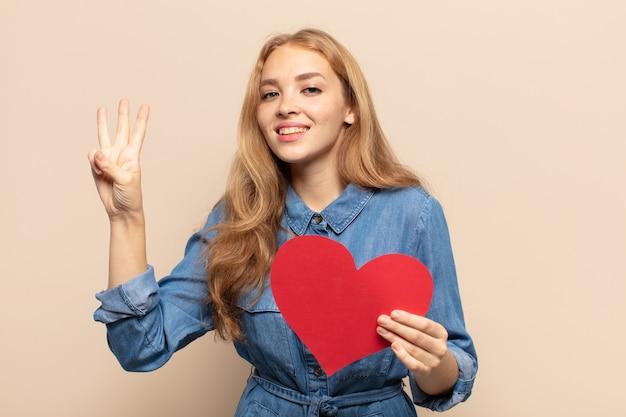 Blondynka uśmiecha się i wygląda przyjaźnie, pokazując numer trzy lub trzeci z ręką do przodu, odliczając w dół