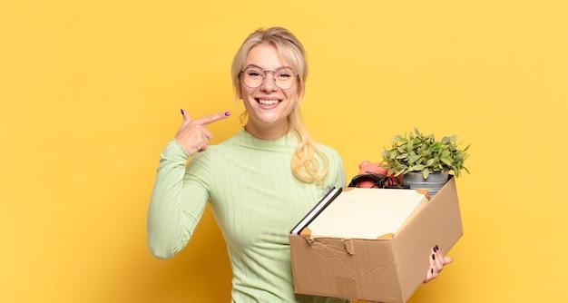 Blondynka uśmiecha się pewnie, wskazując na swój szeroki uśmiech, pozytywne, zrelaksowane, zadowolone nastawienie