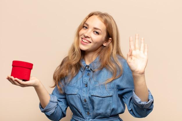 Blondynka uśmiecha się radośnie i wesoło, macha ręką, wita i wita lub żegna się