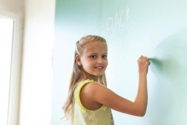 Blondynka uśmiechnięta dziewczyna pisania na tablicy
