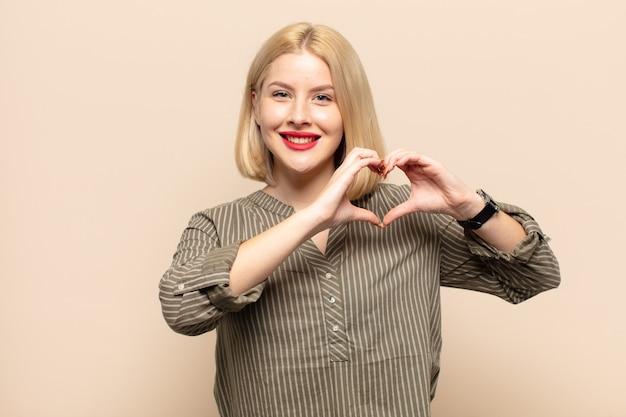 Blondynka uśmiechnięta i czująca się szczęśliwa, słodka, romantyczna i zakochana, tworząc kształt serca obiema rękami