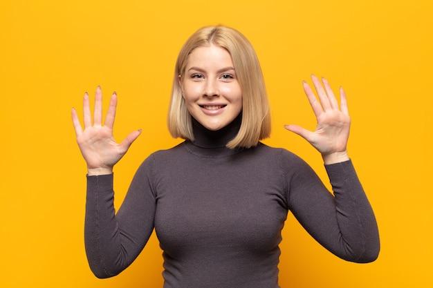Blondynka uśmiechnięta i przyjaźnie wyglądająca, pokazująca dziesiątą lub dziesiątą z ręką do przodu, odliczająca